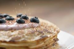 Blini mit Jogurt und Blaubeeren auf hölzerner Tabelle Stockfotos