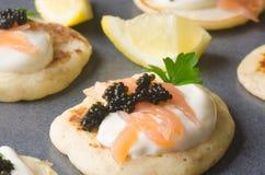 Blini mit Kaviar und geräuchertem Lachs Lizenzfreie Stockfotos