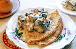 Blini with mushrooms in white sauce. Traditional Russian meal - blini or pancakes garnished with mushrooms in white sauce, white background, back lighting Stock Images