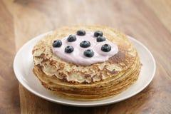 Blini oder Krepps mit Jogurt und Blaubeeren auf hölzerner Tabelle Stockfoto