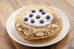 Blini oder Krepps mit Jogurt und Blaubeeren auf hölzerner Tabelle Stockfotos