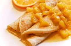 Blini with oranges in sweet sauce. Traditional Russian meal - blini or pancakes garnished with oranges in sweet sauce, white background stock image