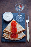 Blini with red caviar and Vodka. On a dark wooden background stock photography