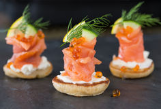 Blini with smoked salmon and sour cream, garnished with dill. Close-up view on dark background royalty free stock photo