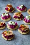 Blinis con remolachas cremosas, queso de cabra y el salmón ahumado caliente Fotografía de archivo