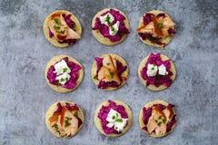 Blinis con remolachas cremosas, queso de cabra y el salmón ahumado caliente Fotos de archivo libres de regalías