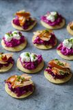 Blinis with creamy beetroot, goat cheese and hot smoked salmon. Party canapes of blinis with creamy beetroot, goat cheese and hot smoked salmon Stock Photography