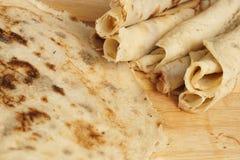 Blinis ou crêpes roulés fraîchement cuits au four sur le conseil en bois photographie stock