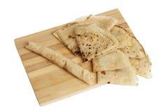 Blinis ou crêpes roulés fraîchement cuits au four sur le conseil en bois photos libres de droits