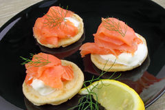 Blinis With Smoked Salmon. Blinis pancakes served with Creme Fraiche, Smoked Salmon and garnished with Dill royalty free stock photo