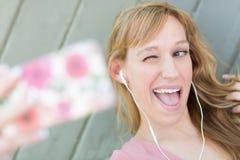 Blinka unga bärande hörlurar för vuxen kvinna som tar en Selfie med hennes Sma Arkivbild