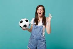 Blinkakvinnafotbollsfan hurrar upp det favorit- laget för service med fotbollbollen som visar reko gest som isoleras på blått arkivfoton