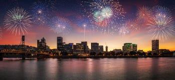 Blinkende Feuerwerke auf einem drastischen Sonnenunterganghimmel mit Portland ODER Stadtbild mit Willamette-Fluss Stockbild