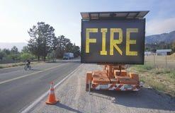 Blinkendes Landstraßenzeichen: Feuer Stockfotos
