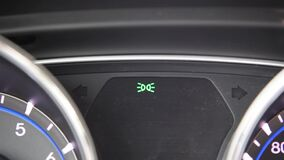 Right turn signal. A blinker or turn indicator on the interior of a car green arrow shows right stock video footage
