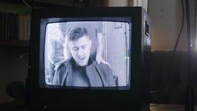 Blinkiing在有播放年轻男性歌手的减速火箭的电视机的屋子里闪动 股票录像