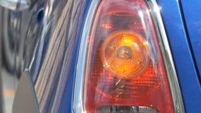 Blinking car left light. Pan shot to a car left rear light signaling stock video footage