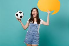 Blinking funny girl football fan cheer up support team with soccer ball empty blank yellow Say cloud speech bubble. Isolated on blue turquoise background royalty free stock image