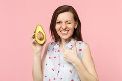 Blinking funny young woman in summer clothes showing thumb up hold fresh ripe green avocado fruit isolated on pink. Pastel background. People vivid lifestyle stock images
