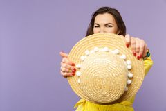 Blinking funny young woman in yellow dress covering face with summer hat, looking camera  on pastel violet. Background in studio. People sincere emotions stock photography