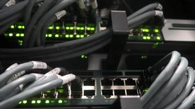 Blinking network ethernet switch with connected cables in server room. The video has a soft effect. stock video