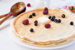 Blintzes (crepes) with butter, berries and honey, holiday food Stock Photography