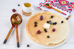 Blintzes (crepes) with butter, berries and honey, holiday food Stock Image