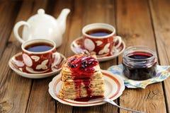 Bliny russe avec de la confiture de groseille, tasses de thé, pot sur le backgrou en bois Image stock