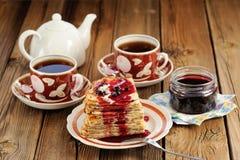 Bliny russo con l'inceppamento del ribes, tazze di tè, vaso sul backgrou di legno Fotografia Stock