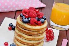Bliny w talerzu z świeżymi jagodami i sokiem pomarańczowym na drewnianym stole fotografia royalty free