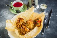 Bliny z mięsem, pomidor, kwaśna śmietanka i filiżanka herbata, obraz royalty free