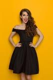 Blinzeln der eleganten Frau im schwarzen Kleid Stockfotos