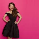 Blinzeln der Frau im eleganten schwarzen Kleidercocktailkleid Stockfotos