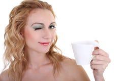 Blinzeln der Frau mit Becher Kaffee/Tee Lizenzfreies Stockbild