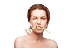 Blinzeln der Frau mit Blume im Mund Stockbilder