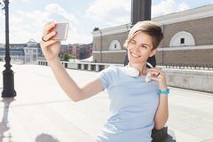 Blinzeln der lächelnden Frau, die selfie mit Telefon auf Straße tut Lizenzfreies Stockbild