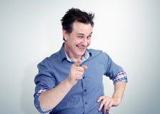 Blinzeln des glücklichen Mannes, der seinen Finger an Ihnen auf Hintergrund zeigt Lizenzfreie Stockbilder