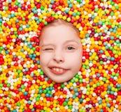 Blinzeln des Kindes, das in den Süßigkeiten aufwirft Stockbilder