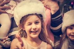 Blinzeln des Kindes, das Kamera mit Zustimmungsgeste während der Weihnachtsfeiertage betrachtet Stockbild
