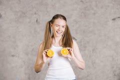 Blinzeln des Mädchens mit Orangen Lizenzfreies Stockbild