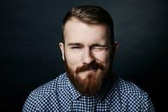 Blinzeln des roten bärtigen Mannstudioporträts auf dunklem Hintergrund Stockfotografie