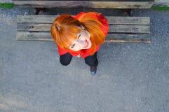 Blinzeln des roten behaarten netten jungen Mädchens an der Schemelvogelschau Lizenzfreie Stockbilder
