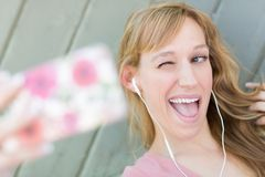 Blinzeln von den jungen erwachsene Frauen-tragenden Kopfhörern, die ein Selfie mit ihrem Sma nehmen Stockfotografie