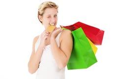 Blinzeln von Frauenbissen auf ihrer Kreditkarte Lizenzfreie Stockfotografie