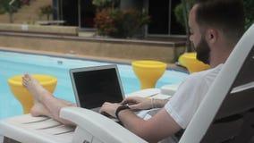 Blisko basenu brodatego mężczyzna szybko pisać na maszynie tekst na laptopie na deckchair zbiory wideo