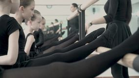 Blisko do rzędu balerin nogi ubierać w czerni tło nauczyciel i przy pójść wzdłuż baletniczego barre i koryguje zbiory
