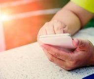 Blisko młoda kobieta modniś gawędzi w ogólnospołecznej sieci przez telefonu komórkowego Zdjęcie Stock