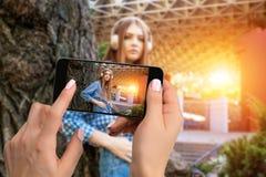 Blisko wręcza mienie telefon komórkowego z fotografii kamery trybem na ekranie wizerunek kobieta Cropped wizerunek portret a obraz royalty free