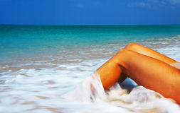 Bliss. View of nice smooth women's legs getting splashed by tropical water royalty free stock image