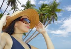 Bliss. Portrait of nice woman in sailor hat and sunglasses in tropical environment royalty free stock photos